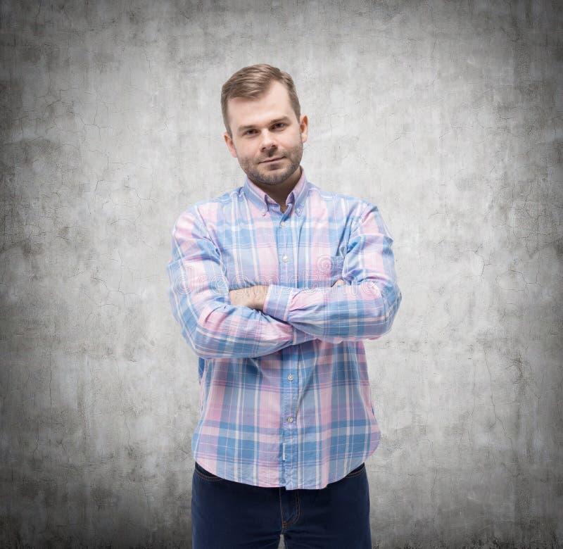 Jonge mens in toevallig overhemd met gekruiste handen Concrete muur stock foto's