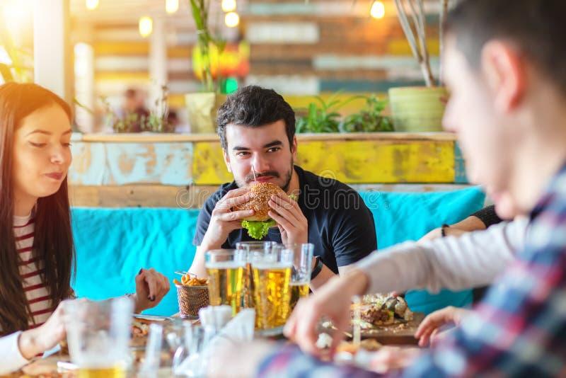 Jonge mens van hamburger genieten en vriendenbedrijf die bij snel voedselrestaurant stock afbeelding