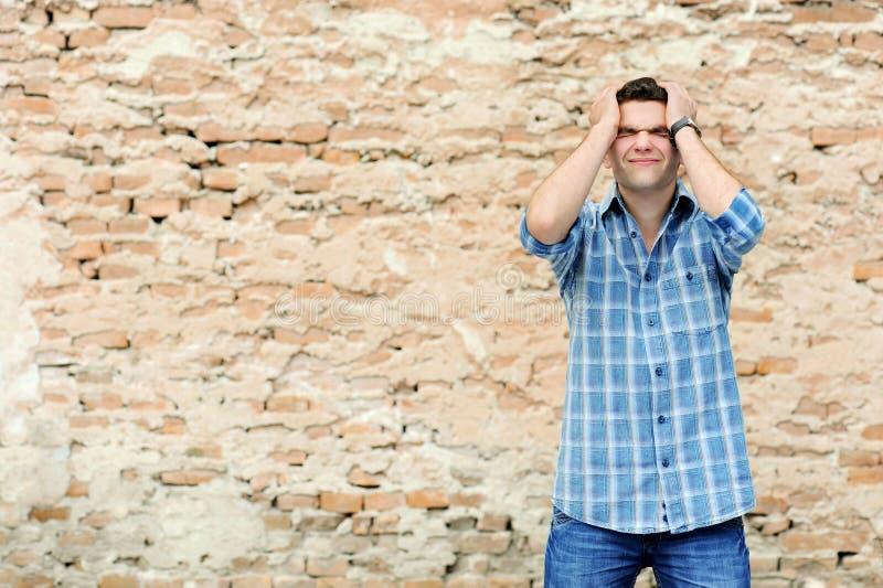 Jonge mens in wanhoop dichtbij bakstenen muur stock afbeeldingen