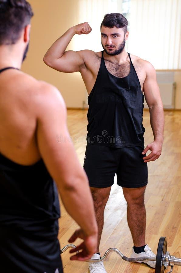 Jonge Mens zich Bevindt Sterk in Front Of een Spiegel en Buigend Spieren - Spier Atletische Bodybuildergeschiktheid Modelposing a royalty-vrije stock fotografie