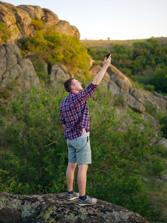 Jonge mens zonder Internet op een natuurlijke achtergrond Reiziger die rotsen voor beter verbindingsconcept beklimmen De ruimte v royalty-vrije stock afbeeldingen