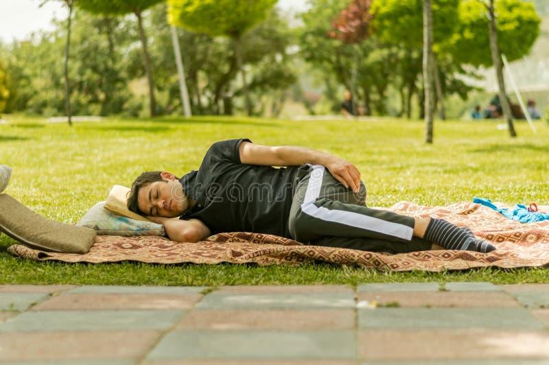 Jonge mens in zwarte kledingsslaap op grassen in een openbaar park royalty-vrije stock afbeeldingen