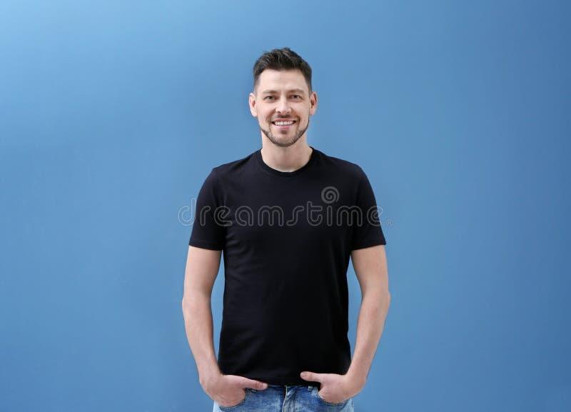 Jonge mens in zwarte t-shirt op kleurenachtergrond stock afbeelding