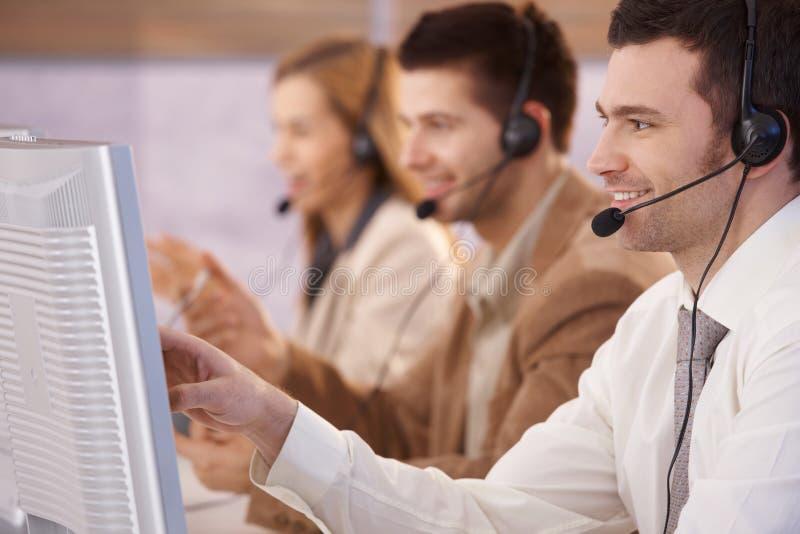 Jonge mensen die in callcenter het glimlachen werken stock afbeeldingen