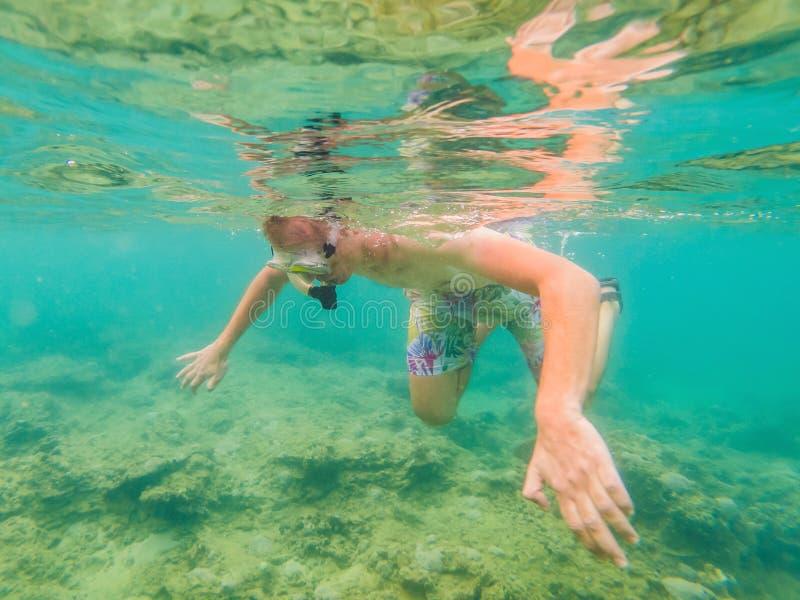 Jonge mensen die onderzoekend de onderwaterachtergrond van het koraalriflandschap in de diepe blauwe oceaan met kleurrijke vissen stock afbeeldingen