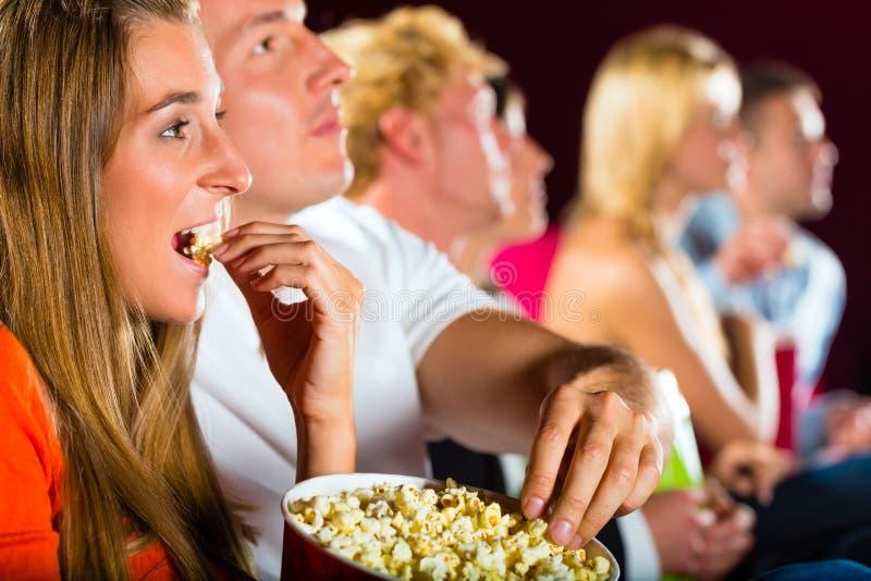 Jonge mensen die op film letten bij bioscoop royalty-vrije stock foto's
