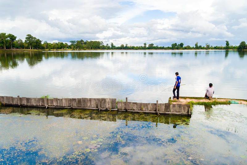 Jonge mensen die in Srah Srang van Angkor Wat vissen stock foto's