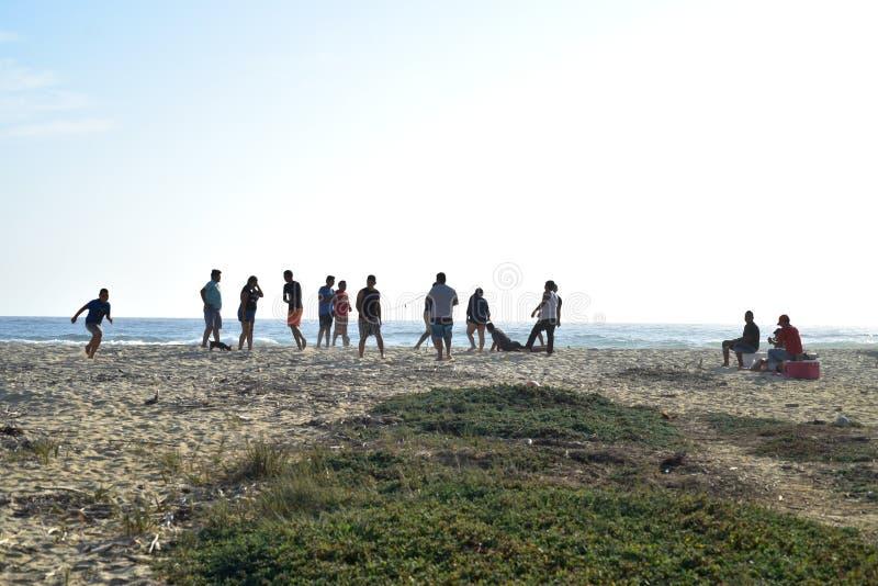 Jonge mensen die volleyball op strand spelen bij schemer in Baja, Mexico royalty-vrije stock foto's
