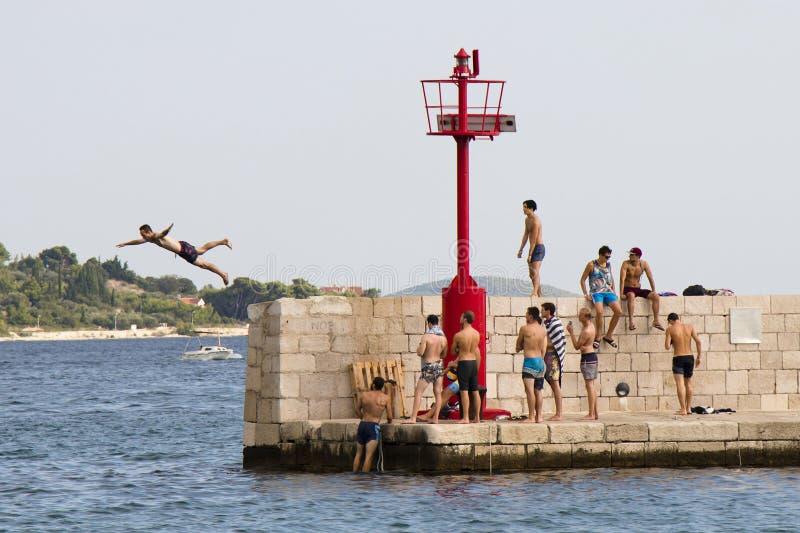 Jonge mensen die in zwempakken op een mens letten springend van de pijler stock foto