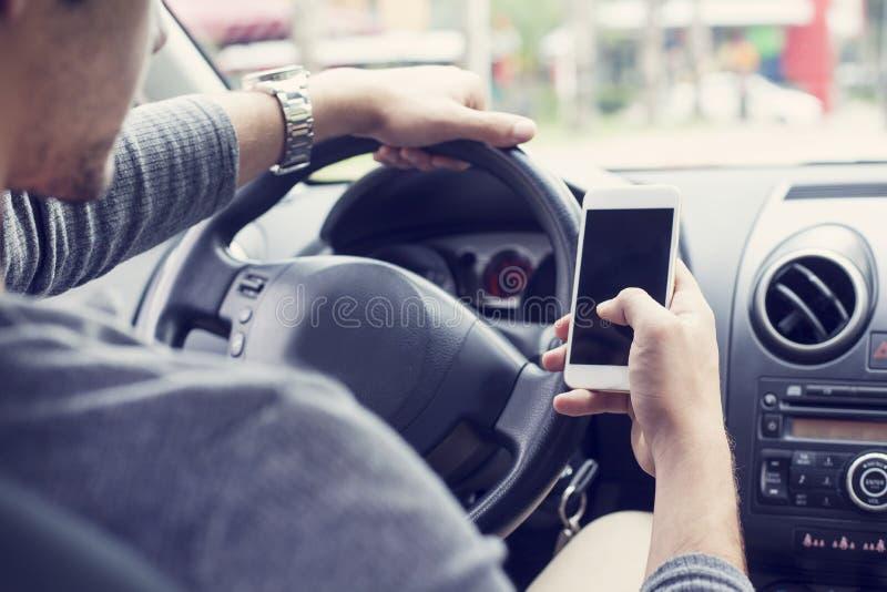 Jonge mensen drijfauto en het gebruiken van mobiele telefoon stock afbeeldingen