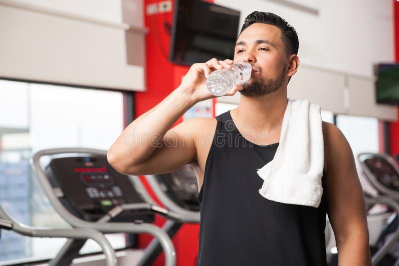 Jonge mensen drinkwater in een gymnastiek stock afbeeldingen