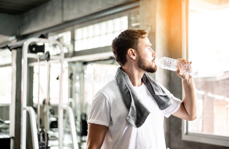 Jonge mensen drinkwater in gymnastiek na oefening stock afbeelding