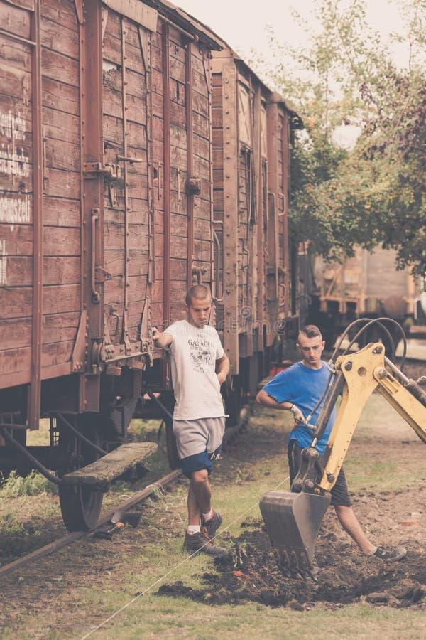 Jonge mensen en graver op het werk stock afbeelding