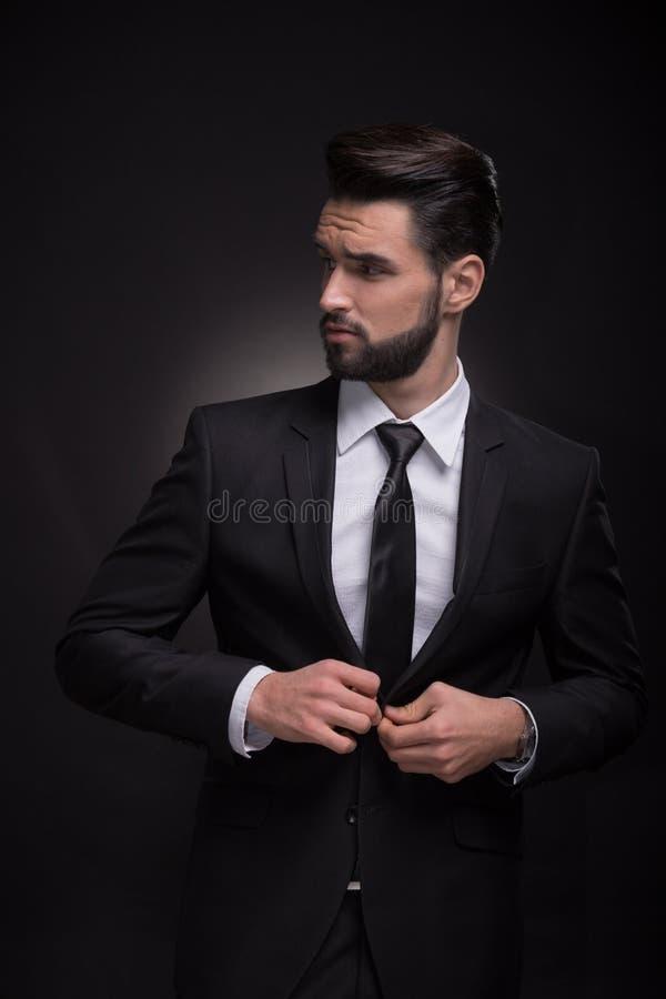 Jonge mensen het elegante kostuum dichtknopen, die zijdelings eruit zien royalty-vrije stock afbeelding