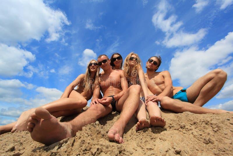 Jonge mensen op een zand stock afbeelding