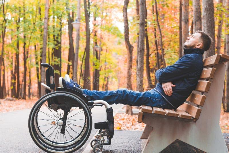 Jonge mensen rustende zitting op een bank met zijn benen op zijn rolstoel royalty-vrije stock foto's
