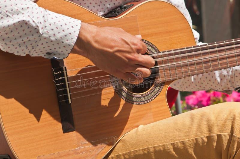 Jonge mensen` s hand die een gitaar in Madrid, Spanje tokkelen stock foto's
