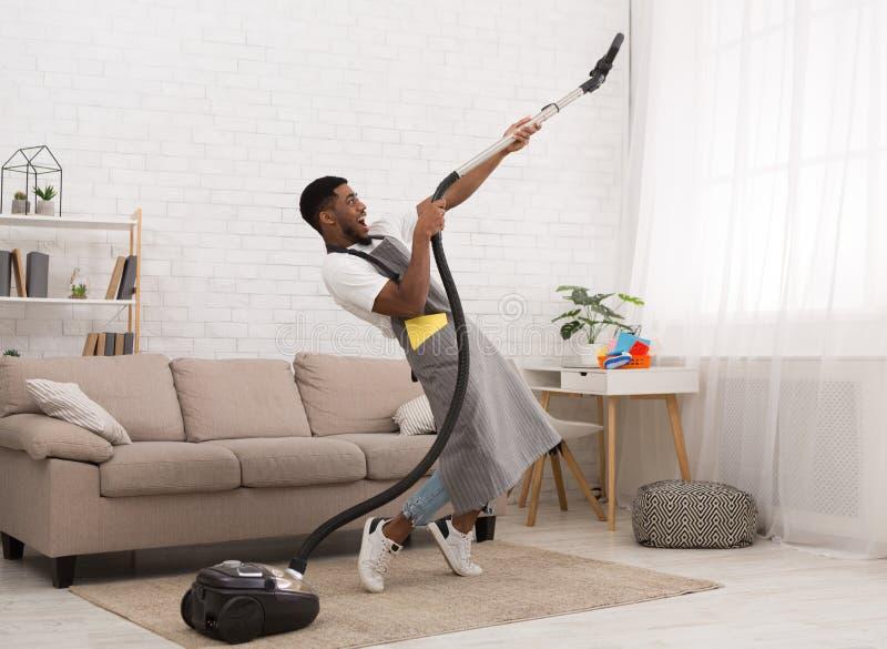 Jonge mensen schoonmakend huis met stofzuiger royalty-vrije stock foto