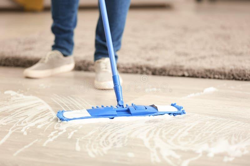 Jonge mensen schoonmakende vloer in zijn vlakte stock afbeeldingen