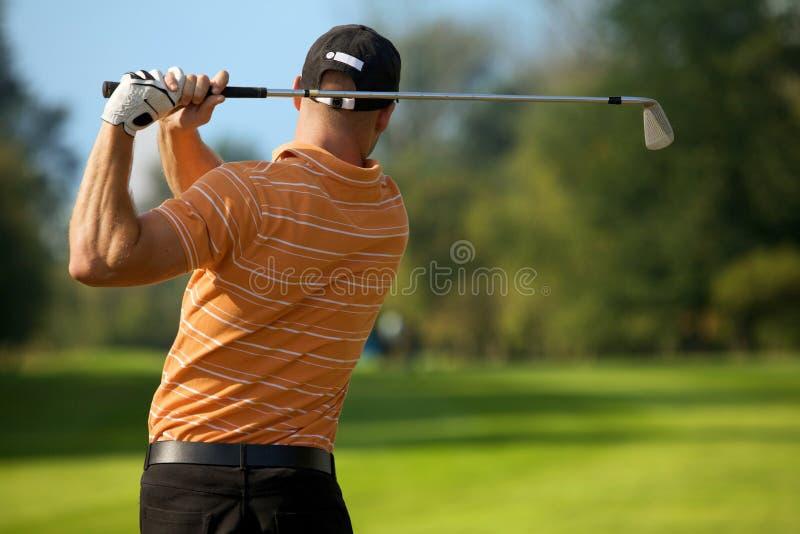 Jonge mensen slingerende golfclub, achtermening stock afbeelding