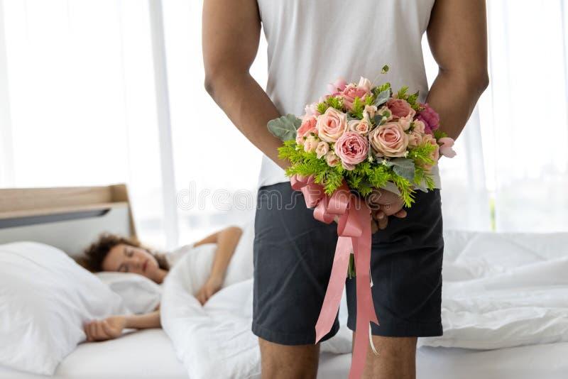 Jonge mensen verbergend boeket van bloem achter zijn rug vóór verrassing zijn vrouw Mooi romantisch paar in bedruimte stock fotografie
