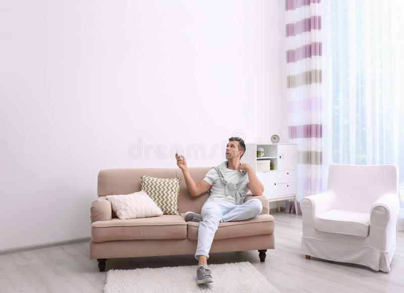 Jonge mensen werkende airconditioner met afstandsbediening royalty-vrije stock afbeelding