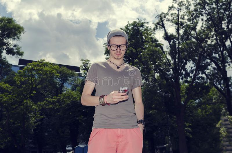 Jonge mensenbankwezen van zijn telefoon in een stadspark royalty-vrije stock fotografie