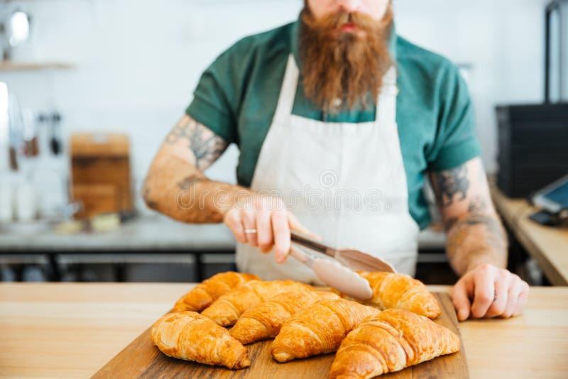 Jonge mensenbarista met baard die croissant nemen die tang met behulp van royalty-vrije stock afbeelding