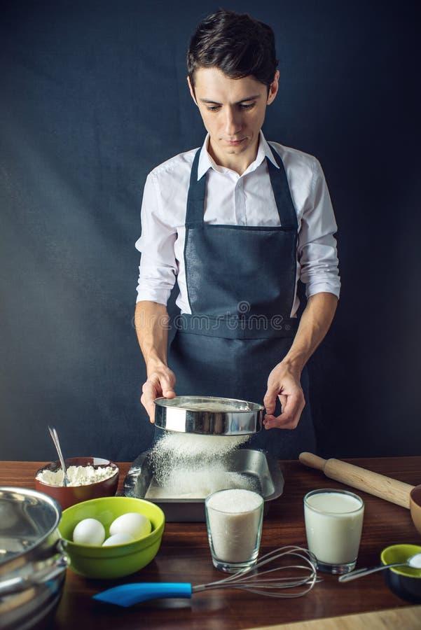 Jonge mensenchef-kok in zwarte schort kokende cake met ingrediënten op de lijst in de keuken Concept de desserts van de mensenkok royalty-vrije stock afbeeldingen