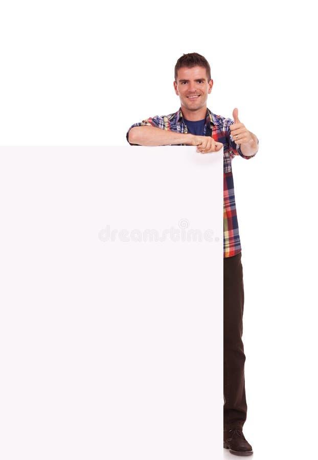 Jonge mensenduimen omhoog achter banner stock fotografie