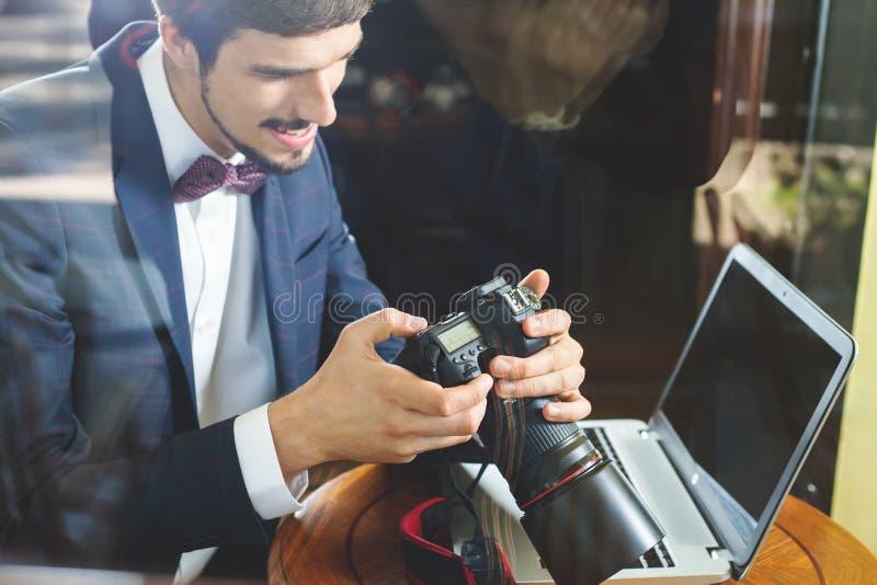Jonge mensenfotograaf die bij koffie werken, die dslr camera met behulp van royalty-vrije stock afbeeldingen
