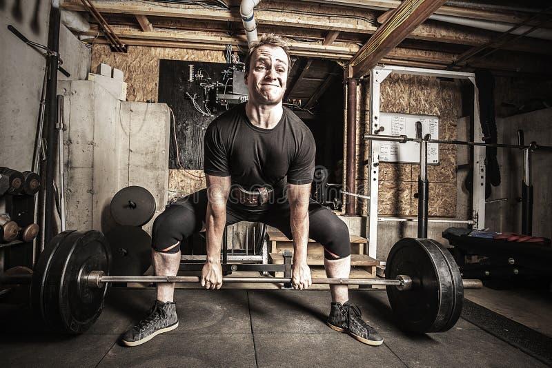 Jonge mensengewichtheffen in een zanderige kelderverdiepingsgymnastiek stock foto