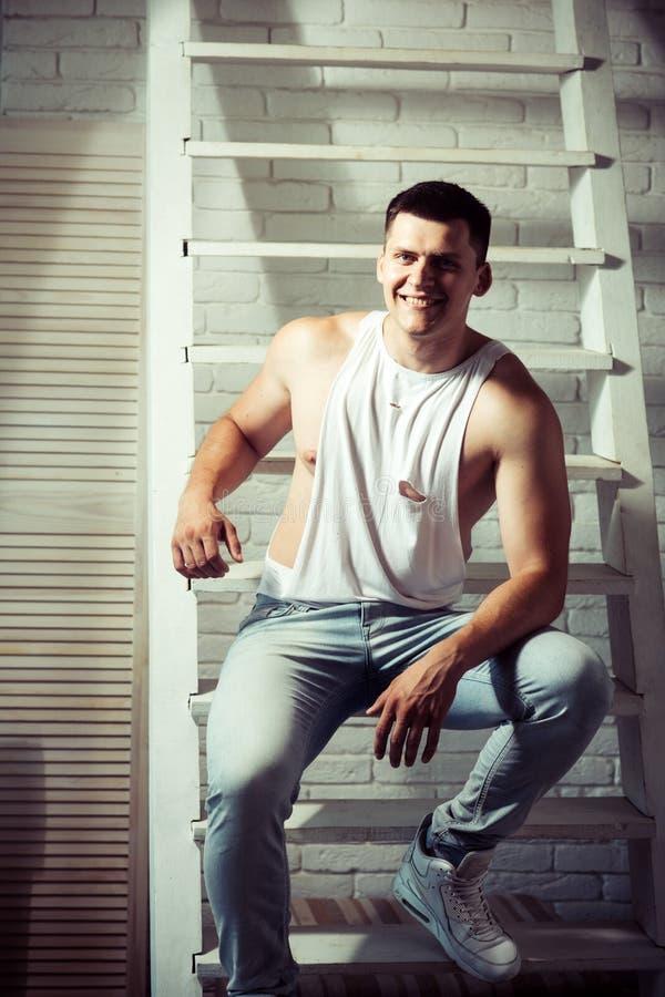 Jonge mensenglimlach op ladder Kerel op in mouwloos onderhemd en jeansmanier Atletische macho met spierborst en handen stock fotografie