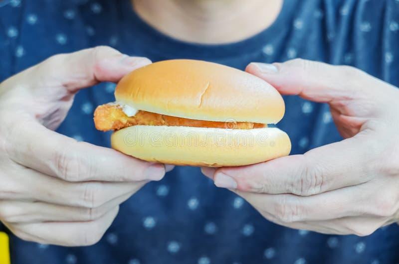 Jonge mensenholding in de mannelijke hamburger van het handen snelle voedsel, Amerikaanse ongezonde calorieënmaaltijd op achtergr stock afbeeldingen