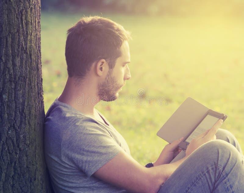 Jonge mensenlezing eBook royalty-vrije stock foto