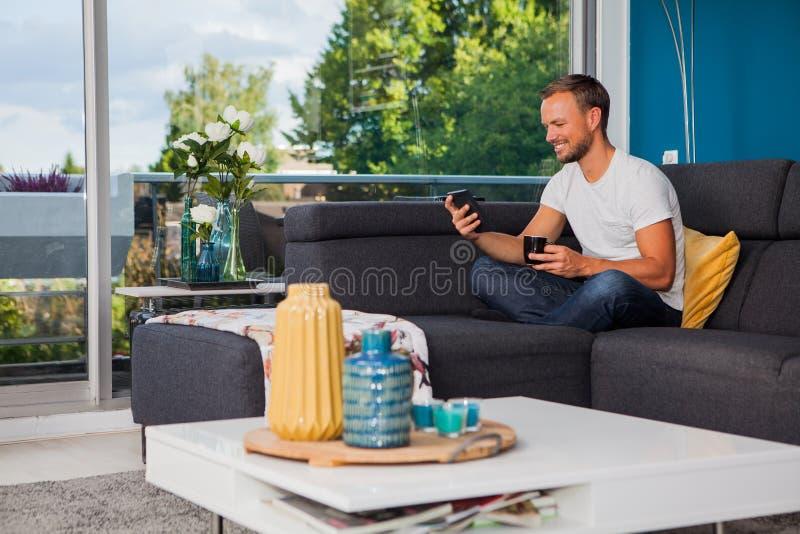 Jonge mensenlezing van een ebooklezer terwijl het drinken van koffie op de laag stock afbeelding