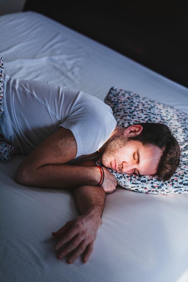 Jonge mensenontwaken in bed in de ochtend royalty-vrije stock fotografie