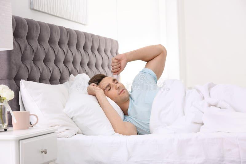 Jonge mensenontwaken in bed met hoofdkussens stock fotografie