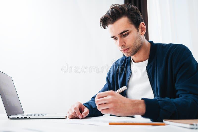 Jonge mensenontwerper die bij de moderne zitting van de zolderstudio bij lijst werken terwijl het werken aan laptop stock foto
