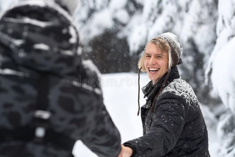 Jonge Mensenpaar die in Sneeuw Forest Outdoor Guys Holding Hands lopen royalty-vrije stock afbeeldingen