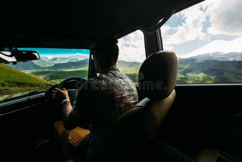 Jonge Mensenreiziger die een Auto in de Bergen in de Zomer, Achtermening van de Auto drijven royalty-vrije stock afbeelding