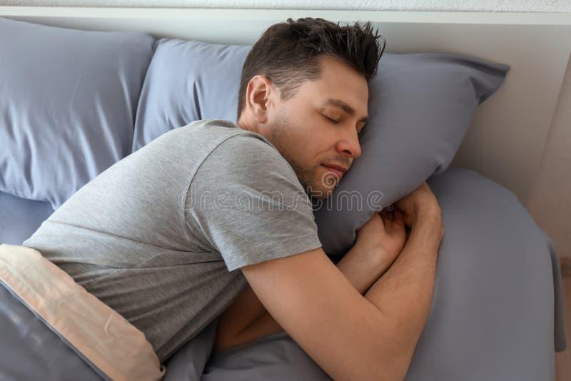 Jonge mensenslaap in bed royalty-vrije stock afbeelding