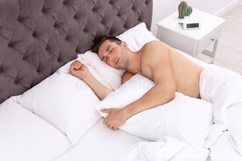 Jonge mensenslaap in bed thuis royalty-vrije stock afbeelding