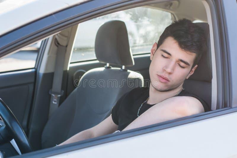 Jonge mensenslaap bij het wiel die zijn auto drijven stock fotografie
