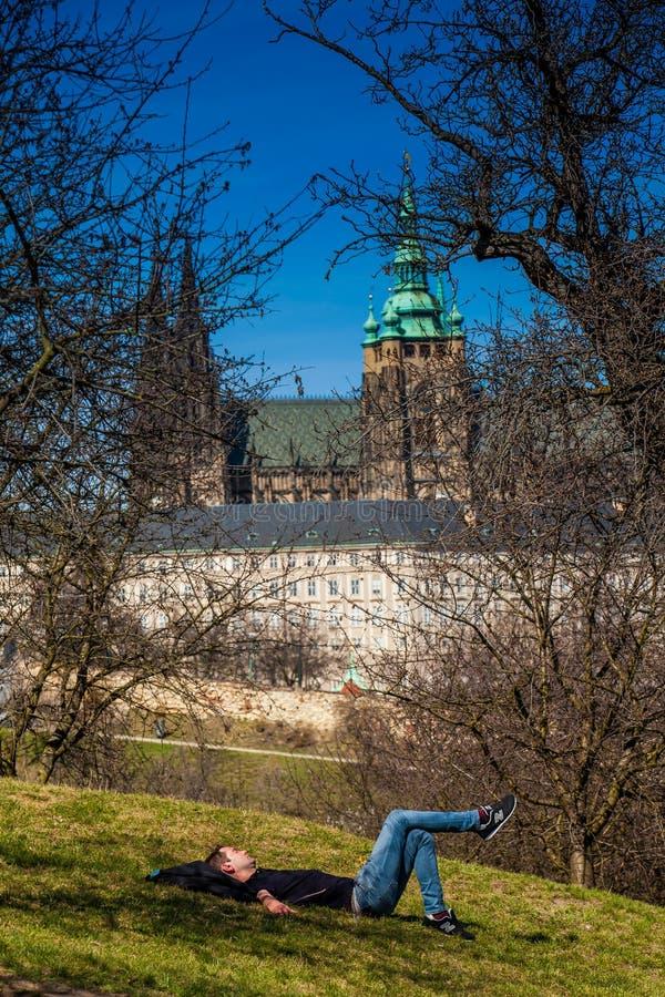 Jonge mensenslaap onder de bomen van het Petrin-Park met de Kathedraal van Praag op achtergrond stock fotografie