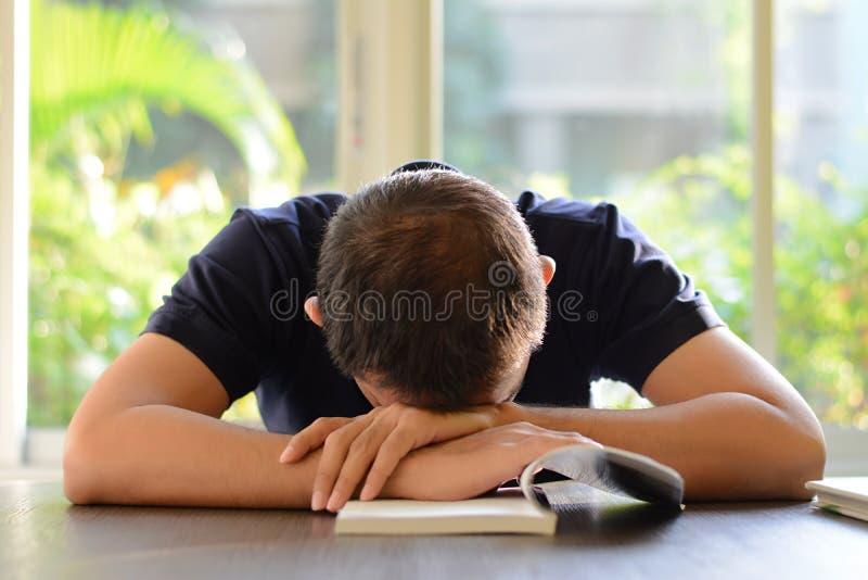 Jonge mensenslaap op de lijst met geopend boek royalty-vrije stock afbeelding