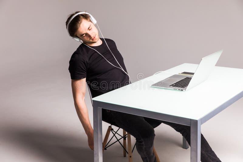Jonge mensenslaap terwijl het dragen van hoofdtelefoons en het werk aangaande laptop op zijn bureaulijst aangaande witte achtergr stock foto