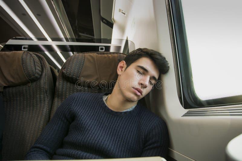 Jonge mensenslaap terwijl het reizen op een trein stock afbeeldingen