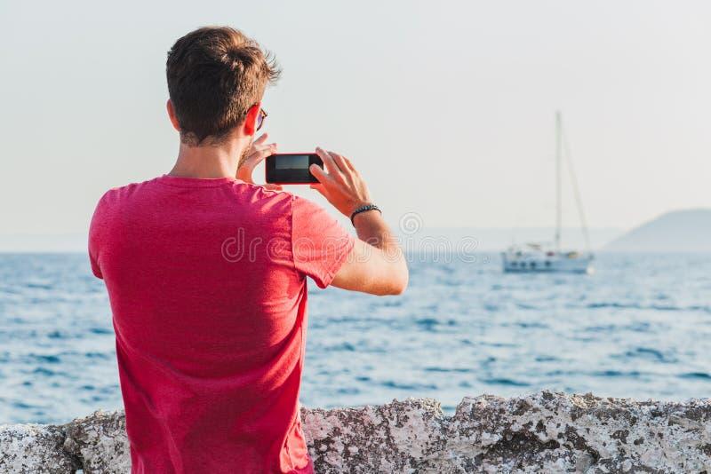 Jonge mensentoerist die foto met smartphone nemen door het overzees stock foto