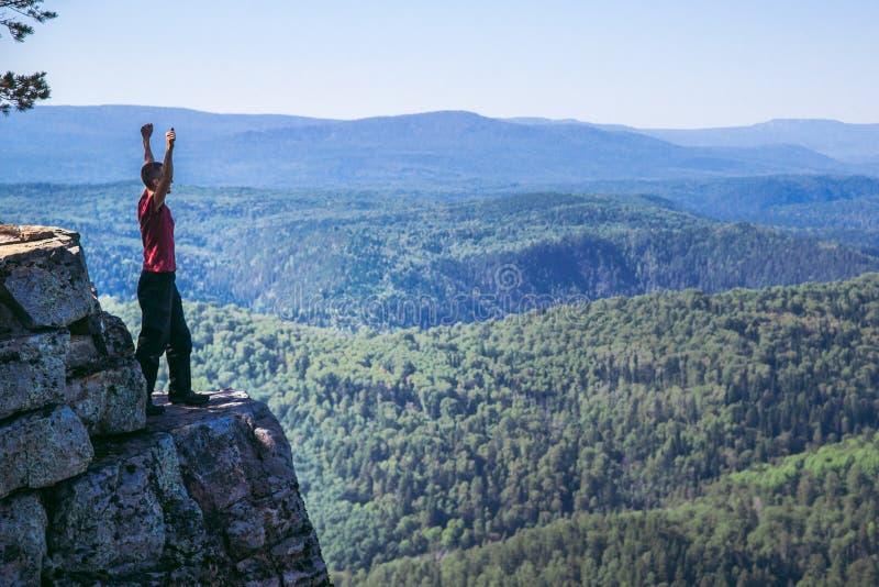Jonge mensenwandelaar die zich bovenop een berg met opgeheven op handen, het vieren succes bevinden Volledige lengtespruit met ex stock fotografie